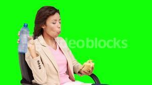 Businesswoman eating sandwich for lunch