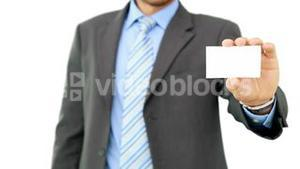 Young businessman showing card to camera