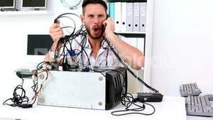 Angry technician pulling wires in broken computer