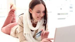 Pretty brunette using laptop on her bed to shop online