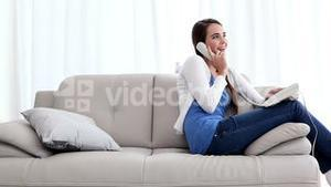 Pretty brunette talking on phone on the couch