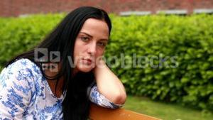 Sad brunette thinking on bench in the park