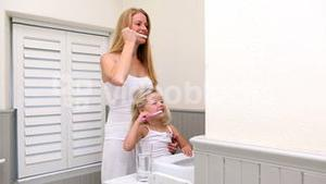 Cute little girl brushing her teeth with her mother