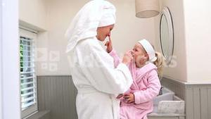 Mother and daughter putting face cream on
