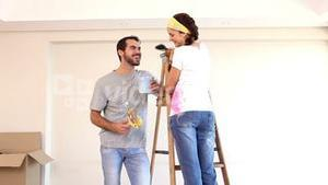 Attractive couple painting their living room