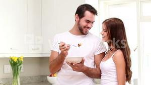 Attractive couple eating cereal in the morning