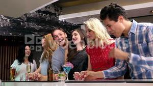 Attractive friends drinking shots together
