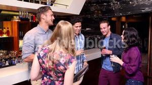 Attractive friends dancing and drinking at the bar
