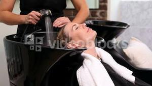 Pretty woman getting her hair washed