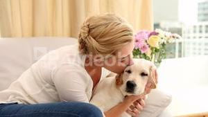 Happy blonde playing with puppy on the couch