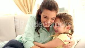 Happy mother and daughter on the couch