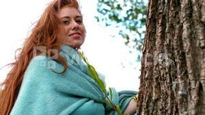 Pretty redhead wrapped in blanket by a tree