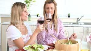 Attractive women drinking wine eating salad