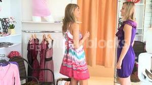 Charming women trying dresses together