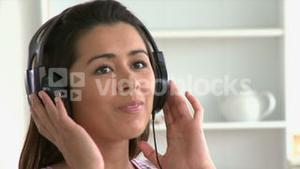 Cheerful asian woman listen to music wearing headphones