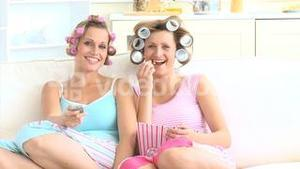 Relaxed women eating popcorn wearing hair rollers