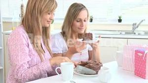 Jolly young women eating chocolate cake