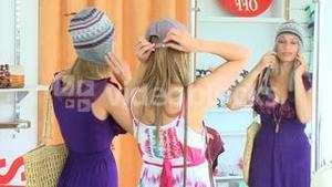 Positive women wearing hat looking at the mirror