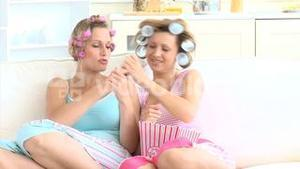 Amused woman with hair roller watching tv with her friend