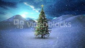 Snow falling on christmas tree in snowy landscape