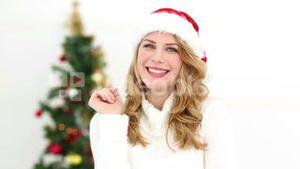 Festive blonde smiling at camera after getting an idea