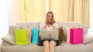 Excited blonde shopping online on couch
