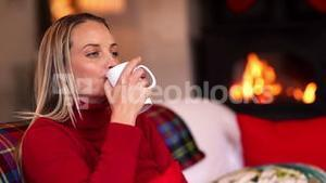 Pretty blonde enjoying a hot drink on the couch