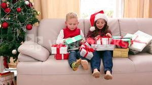 Cute siblings sitting on couch with lots of christmas gifts