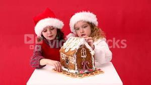 Cute festive sisters making a ginger bread house