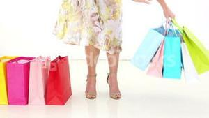 Woman picking up many shopping bags