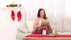 Pretty brunette relaxing on the couch at christmas time