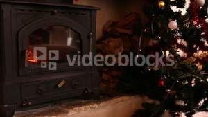 Fire burning in fireplace beside christmas tree