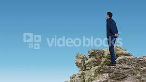 Businessman and woman standing on rocks looking out