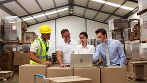 Warehouse managers looking at laptop