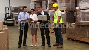 Warehouse managers and worker talking