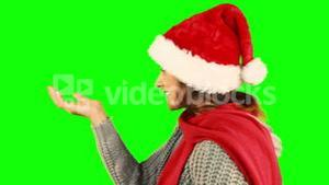 Girl in santa hat and warm clothing blowing over hands