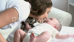 Young delighted mother taking care of her baby