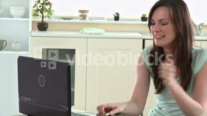 Excited woman phoning and using her laptop