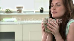 Relaxed woman drinking coffee in the kitchen
