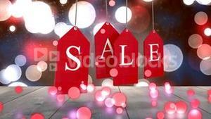 Red sale tags hanging against glowing background