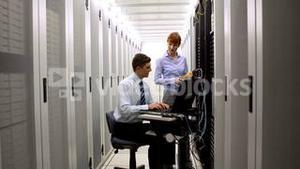 Technicians using digital cable analyzer on server
