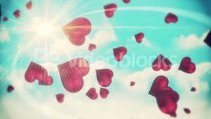 Pink hearts floating against blue sky