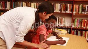 Teacher helping pupil and smiling at camera