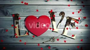 Heart confetti falling on golden love text with heart lock