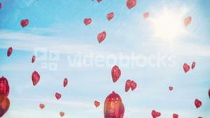Red hearts floating against blue sky