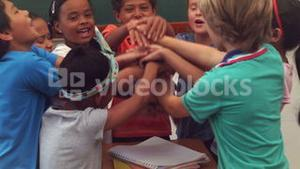 Pupils holding hands together and cheering in classroom