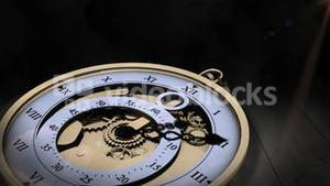 Pocket watch ticking on wooden surface