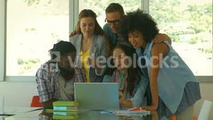 Students looking at laptop together
