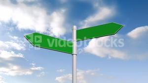 Green signpost against blue sky