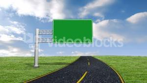 Green road sign against blue sky